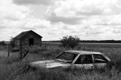 Abandoned Car. A black and white image of an old abandoned car in the middle of a tall hay field Stock Photos