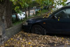 Abandoned car covered in leaves in the autumn