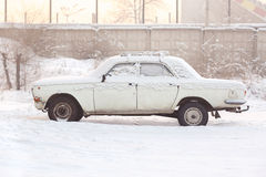 Abandoned car covered with snow in winter at sunset, warm tones, side view. Rusting, recycling, metal processing, write Stock Image