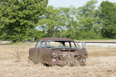 Abandoned Car In Field. Abandoned car in a field with railroad tracks stock photo