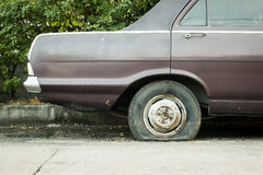 Abandoned car with flat tire stock images