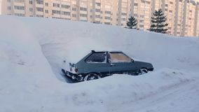 Abandoned car littered with snow parking lot in city, snowstorm stock video
