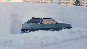 Abandoned car littered with snow parking lot in city, snowstorm stock video footage