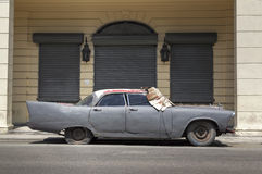 American classic car in Havana, Cuba. A classic american car, abandoned and parked in front of an old and closed boutique in Prado, Havana Stock Image