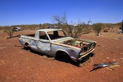 Abandoned car in Outback Australian ghost town. An old pick up truck utility lies abandoned in the Australian outback with blue sky and red soil royalty free stock photo
