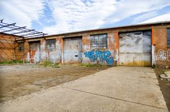 Abandoned car repair workshop. Hobart, Tasmania, February 6, 2016: Exterior view of an abandoned Car repair workshop, with grafitti on walls, Hobart, Tasmania Royalty Free Stock Images