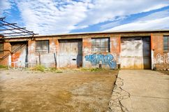Abandoned car repair workshop. Hobart, Tasmania, February 6, 2016: Exterior view of an abandoned Car repair workshop, with grafitti on walls, Hobart, Tasmania Stock Image