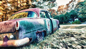 Abandoned car rusting in a field Stock Photos
