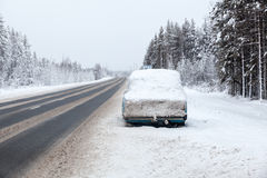 Abandoned car on the side of winter road, covered with snow. The Royalty Free Stock Image