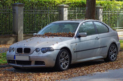 Abandoned car. On the street covered by autumn leaves stock photography