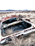 An abandoned car with tumbleweeds Stock Image