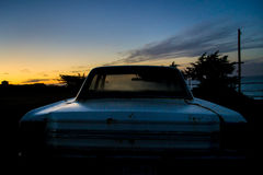 Abandoned car in the twilight. Abandoned car against the sunset at the beach Royalty Free Stock Photos