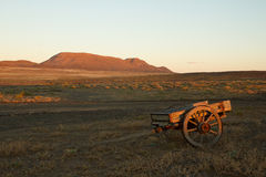 Abandoned cart. A semi-arid landscape with an abandoned cart in the foreground Royalty Free Stock Photography