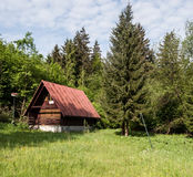 Abandoned chalet on meadow with trees around. And blue sky with clouds on Dierova settlement near Orava river and Kralovany city in Slovakia royalty free stock image