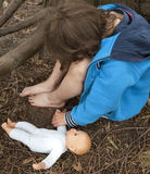 Abandoned child. Young and sad child with a doll hiding under a tree Stock Image