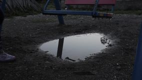 Abandoned children`s playground, innocence sad child swinging on a swing. reflection in puddles. Abandoned children`s playground, innocence sad child swinging stock video