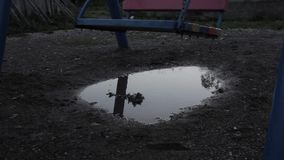 Abandoned children`s playground, innocence sad child swinging on a swing. reflection in puddles. Abandoned children`s playground, innocence sad child swinging stock footage
