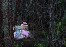 Abandoned childs doll and soft toy on swing Royalty Free Stock Photo