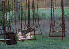 Abandoned childs doll and soft toy on swing Royalty Free Stock Photography