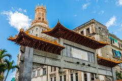 Abandoned chinatown arch and old slums in the background, Havana. Cuba Royalty Free Stock Images