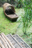 Abandoned chinese bamboo boat in green water Royalty Free Stock Photography