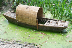 Abandoned chinese bamboo boat in green water Stock Photo