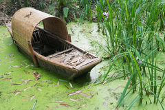 Abandoned chinese bamboo boat in green water Royalty Free Stock Images
