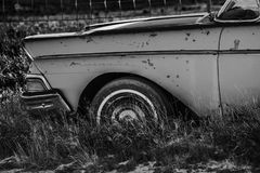 Abandoned Classic Car. Vintage Abandoned Classic Car in the Grass Somewhere in the Colorado, United States of America. Aged Vehicle Closeup in Black and White Stock Photo