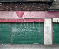 Abandoned closed shop with decaying facade. And green shutters Stock Image