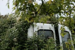 Abandoned commercial vehicle seen stuck in a hedgerow. royalty free stock images
