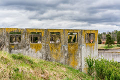 Abandoned concrete ruin on grass hill with square openings against cloudy sky. Royalty Free Stock Images