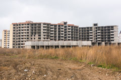 Abandoned construction of multi storey residential complex, overgrown with weeds Royalty Free Stock Photography