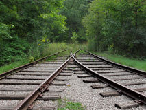 Abandoned converging railroad tracks. Two sets of abandoned railroad tracks converging in the woods royalty free stock photography
