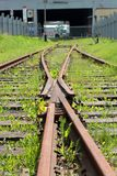 Abandoned converging railway tracks against a wall Stock Photography