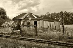 Abandoned Cottage Beside Railway Tracks. A monotone image of an abandoned and crumbling old worker`s cottage and shed beside railway tracks royalty free stock photos