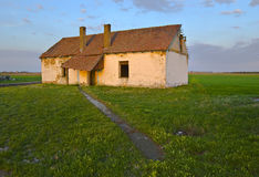 Abandoned country house. Narrow road leads to the old ruined and abandoned country house in the middle of nowhere stock photo
