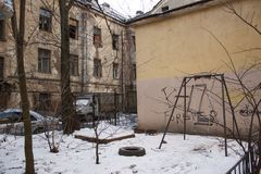 Abandoned courtyard, ruined houses, old swings Stock Photo