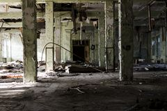 Abandoned and dangerous production premise with trash on floor. Inside an abandoned deserted cluttered industrial building Royalty Free Stock Image