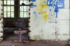 Abandoned and dangerous production premise with trash on floor. Inside an abandoned deserted cluttered industrial building with broken chair in center Stock Photo