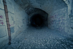 Abandoned dark creepy and claustrophobic tunnel, with write on brick wall. Desolation concept royalty free stock images