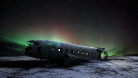Abandoned DC plane in Iceland with aurora northern light and star background stock photography