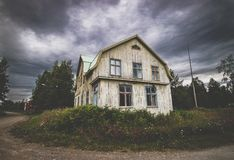 Abandoned, decaying old house by a road and dramatic sky Royalty Free Stock Image