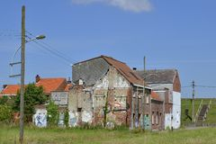 Abandoned and demolished houses, Doel, Belgium. Rough walls of abandoned house that has graffiti on it, depicting olympic rings; ghost town Doel, East Flanders royalty free stock photography