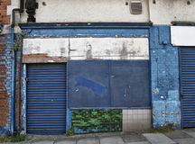 Abandoned derelict shop with storefront boarded up. With peeling blue paint decaying facade and exposed tiles and brickwork stock images
