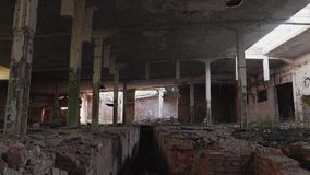 Abandoned destroyed factory. The sun`s rays Shine through the holes in the walls. stock footage