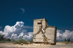 Abandoned and destroyed a small house. Lonely and desolate destroyed a small house on the beach under the hot summer cloudy sky Stock Photo