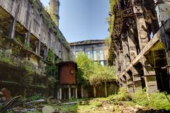 Abandoned, destroyed by war and overgrown machinery of Tkvarcheli power plant Royalty Free Stock Image
