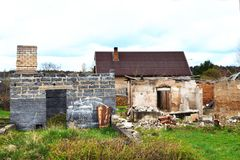 Two abandoned houses. Abandoned and devastated house with fallen facade and roof and broken walls and unfinished abandoned house with bricks chimney in grass stock photo