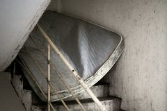 Abandoned dirty mattress blocking stained stairway from under. With handrail inbetween stock image