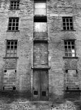 Abandoned disused old derelict factory or mill building. With broken windows Royalty Free Stock Photos